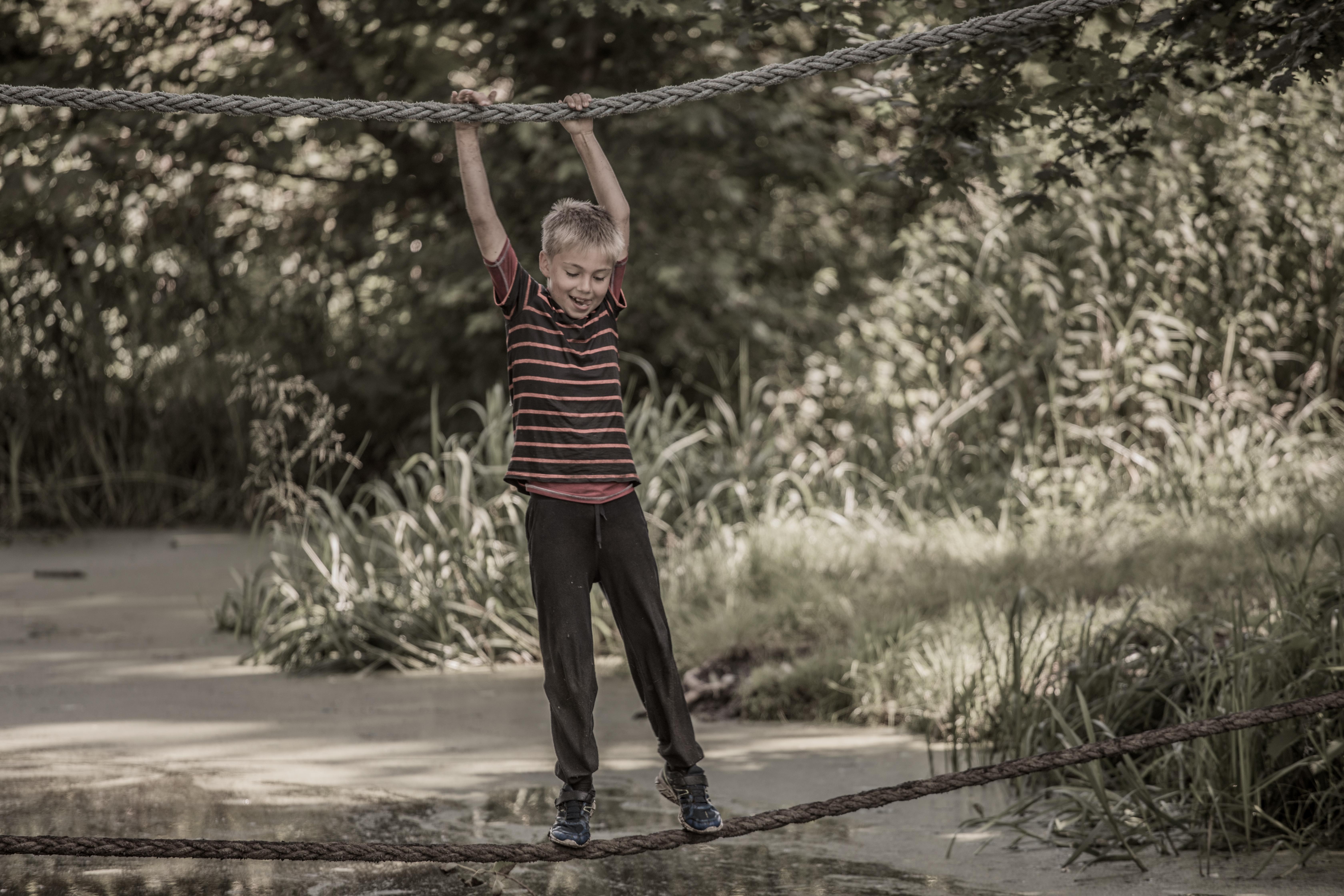 kind loopt over touw van hangbrug